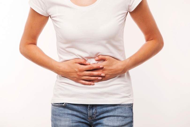 Woman heaving belly ache, on white background