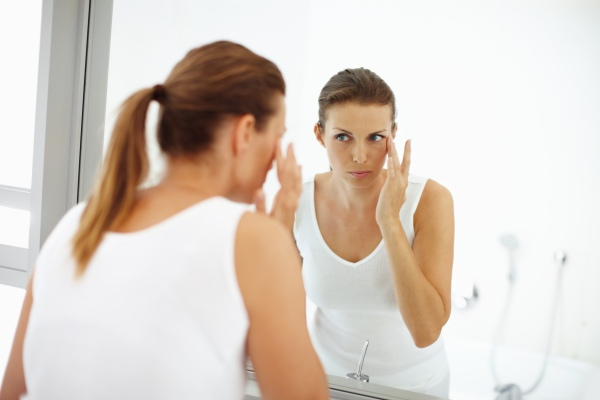 Image of Woman looking into mirror