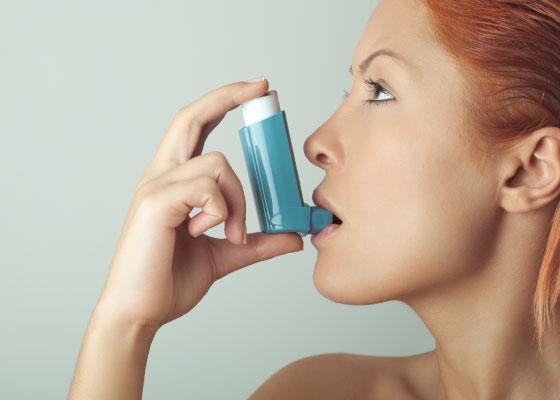 Woman using an inhaler